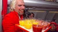 Le milliardaire britannique Richard Branson, le 12 mai 2013, en hôtesse de l'air, à bord d'un vol de la compagnie AirAsia [Tony Ashby / AFP]