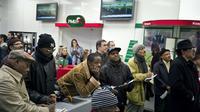 """Des joueurs suivent une course dans la première boutique """"PMU City"""" [Jean-Philippe Ksiazek / AFP/Archives]"""