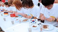 """Sous le """"chapiteau olympique"""" bordant la plage de Leffrinckoucke, assiette, bol, verre et lingette rince-doigts face à eux, les compétiteurs s'assouplissent les doigts pour remporter un titre prestigieux : celui du meilleur décortiqueur de crevettes grises.[AFP]"""