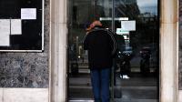 Un homme butte contre la porte fermée de la gare d'Athènes lors de la grève de la fonction publique, le 19 décembre 2012 [Louisa Gouliamaki / AFP]