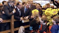 Des enfants présentent des tournesols au président François Hollande (c), le 23 février 2013 au salon de l'agriculture à Paris [Kenzo Tribouillard / AFP]