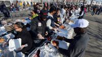 Des volontaires distribuent des repas pour la Thanksgiving aux New-Yorkais victimes de l'ouragan Sandy, le 22 novembre 2012 dans le quartier du Queens [Stan Honda / AFP]