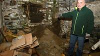 Bertrand Vilain, auteur d'un livre sur l'affaire Seznec, montre un trou dans la cave de la maison où habitait la famille Seznec lors de fouilles le 24 février 2018 [Fred Tanneau / AFP/Archives]