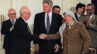Le 28 septembre 1995, le président américain Bill Clinton (C) observe le premier ministre israélien Yitzhak Rabin (2e D) et Yasser Arafat (2e D), dirigeant de l'OLP, se serrer la main après la signature d'un accord, à Washington. [LUKE FRAZZA / AFP/Archives]