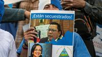 Un Nicaraguayen brandit une pancarte de soutien aux journalistes Miguel Mora et Lucia Pineda, accusés de terrorisme par le régime de Daniel Ortega, lors d'une manifestation le 22 décembre 2018 à San José au Costa Rica [Ezequiel BECERRA / AFP]