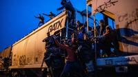 Des migrants illégaux agrippés à un train de marchandises en direction des Etats-Unis, traversent de nuit le village de Las Patronas, le 9 août 2018 dans l'Etat du Veracruz, au Mexique [RONALDO SCHEMIDT / AFP]