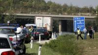Des policiers autour du camion abandonné sur la bande d'arrêt d'urgence d'une autoroute dans lequel des corps en décomposition ont été découverts le 27 août 2015 près de Neusiedl am See en Autriche [DIETER NAGL / AFP]