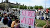 """Des militants anti-racistes derrière une pancarte """"bienvenue aux réfugiés"""" à Dresde le 29 août 2015 [ROBERT MICHAEL / AFP]"""