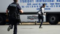 Un policier poursuit un jeune homme suspecté d'être un migrant, dans les environs de Calais le 5 juillet 2017 [DENIS CHARLET / AFP]
