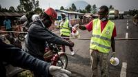 Un conduteur de moto-taxi se fait laver les mains sur la route entre Butembo et Goma, en RD Congo, dans le cadre de la lutte contre l'épidémie d'Ebola, le 16 juillet 2019 [JOHN WESSELS / AFP]