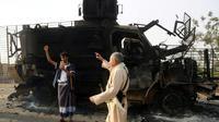 Des hommes armés yéménites inspectent un véhicule détruit après des affrontements entre forces loyalistes et rebelles près du port de Hodeida (ouest), cible d'une offensive du pouvoir aidé par l'Arabie saoudite et les Emirats, le 29 mai 2018 [ABDO HYDER / AFP]