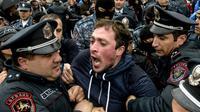 Des policiers arméniniens arrête un manifestant de l'opposition à Erevan, le 21 avril 2018 [Karen MINASYAN / AFP]