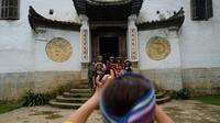 Des touristes posent le 26 octobre 2018 devant un ancien palais Hmong à Dong Van, dans le nord du Vietnam [Nhac NGUYEN / AFP]