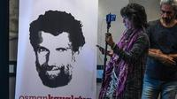 Une journaliste se tient devant une affiche représentant l'homme d'affaires et philanthrope turc Osman Kavala, lors d'une conférence de presse de ses avocats le 31 octobre 2018 [OZAN KOSE / AFP/Archives]