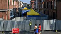 Un policier monte la garde le 5 juillet 2018 devant une barrière interdisant l'accès à une rue d'Amesbury, dans le sud de l'Angleterre, où un couple exposé au Novitchok est tombé malade [Chris J Ratcliffe / AFP]