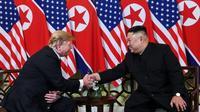Donald Trump et Kim Jong Un se serrent la main au début de leur sommet à Hanoï [SAUL LOEB / AFP]