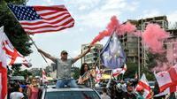 Des manifestants géorgiens brandissent des drapeaux américain et européen lors à Tbilissi le 24 juin 2019 [Vano SHLAMOV / AFP]