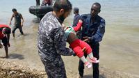 Des membres de la sécurité libyenne portent le corps d'un bébé dans la ville d'al-Hmidiya, après le naufrage au large de la Libye d'une embarcation de migrants dont 100 sont toujours portés disparus, le 29 juin 2018  [Mahmud TURKIA / AFP]