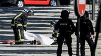 Des policiers recouvrent le corps d'un assaillant, après un attentat avorté sur les Champs-Élysées, le 19 juin 2017 à Paris [Thomas SAMSON / AFP]