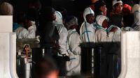 Des migrants attendent pour débarquer du navire italien Diciotti, le 20 juin 2018 à Pozzallo, en Sicile [Giovanni Isolino / AFP]