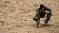 Un soldat américain recueille du sable à Omaha Beach, en Normandie, le 5 juin 2019 [JOEL SAGET / AFP]