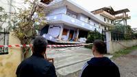 Des Albanais observent une maison effondrée le 28 novembre 2019 à Durres sur la côte Adriatique après un séisme meurtrier [Gent SHKULLAKU / AFP]