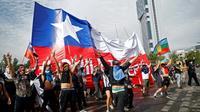 Des manifestants agitant un drapeau géant chilien, à Santiago du Chili le 23 octobre 2019  [Pablo VERA / AFP]