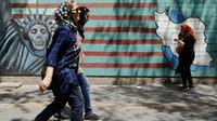 Des Iraniennes passent devant la façade de l'ancienne ambassade des Etats-Unis à Téhéran le 7 août 2018. [ATTA KENARE / AFP]