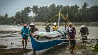 Des pêcheurs mettent un bateau à l'abri avant l'arrivée du typhon Phanfone, à Baybay (Philippines) le 24 décembre 2019 [Alren BERONIO / AFP]