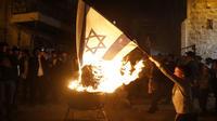 Des Juifs ultra-orthodoxes brûlent un drapeau israélien à Jérusalem, en mai 2018.