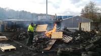 Un employé de la société Arjowiggins jette une palette de bois dans un feu, le 28 janvier 2019 à Jouy-sur-Morin, alors qu'il brûle une partie du stock de l'usine destinée à la production de cartes grises pour réclamer un «plan social digne».