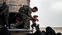 Un combattant des Forces démocratiques syriennes (FDS) durant l'évacuation de femmes et enfants du dernier réduit du groupe Etat islamique (EI), le 26 février 2019 dans la province de Deir Ezzor [Delil SOULEIMAN / AFP]