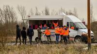 Des membres de l'association Vie Active, mandatée par l'Etat, distribuent des repas aux migrants, le 9 mars 2018 à Calais [PHILIPPE HUGUEN / AFP]