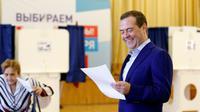 Le Premier ministre russe Dmitri Medvedev sourit en tenant un bulletin dans un bureau de vote à Moscou, le 9 septembre 2018 [Dmitry Astakhov / Sputnik/AFP]