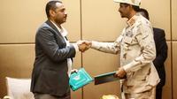 Le numéro deux  du Conseil militaire au pouvoir au Soudan Mohammed Hamdane Daglo (droite) et le leader de la contestation Ahmed Rabie se serrent la main après avoir signé la déclaration constitutionnelle actant la création d'un pouvoir civil, le 4 août 2019 à Khartoum [ASHRAF SHAZLY / AFP]