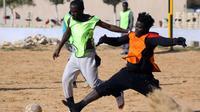 Des migrants Camerounais (orange) et Sénégalais (jaune) participent à un match de football au camp de Tarjoura en Libye, le 28 février 2018 [MAHMUD TURKIA / AFP]