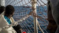 Des migrants à bord du Sea Watch 3 observent un bateau des garde-côtes italiens [FEDERICO SCOPPA / AFP]
