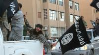 Une image diffusée par l'organe de presse jihadiste Welayat Raqa le 30 juin 2014 montre un membre du groupe État islamique (EI) défila un drapeau de l'EI à la main dans une rue de la ville syrienne de Raqa.  [- / WELAYAT RAQA/AFP/Archives]