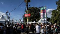 """Des visiteurs traversent la """"Place Maurice Audin"""" à la Fête de l'Humanité, à La Courneuve, près de Paris, le 15 septembre 2018 [Christophe ARCHAMBAULT / AFP]"""