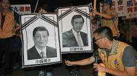 Un militant pour l'indépendance de Taïwan s'apprête à brûler des photos des dirigeants chinois et taïwanais, le 7 novembre 2015 à Taipei [STR / AFP]