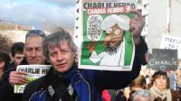 Des manifestants lors de la marche républicaine du 11 janvier 2015 à Paris brandissent des exemplaires du dernier Charlie Hebdo [RAYMOND ROIG / AFP]