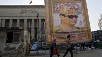 Des Egyptiens marchent devant un immense portrait du général Al-Sissi au Caire, le 27 mars 2014 [Khaled Desouki / AFP/Archives]