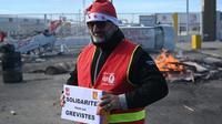 Un militant CGT porte une cagnotte pour les grévistes, lors d'un repas de noël organisé le 24 décembre 2019 au port de Marseille [Christophe SIMON / AFP]