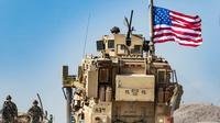 Un véhicule militaire américain lors d'une manifestation de Kurdes près de Ras al-Aïn aux abords de la frontière turque, le 6 octobre 2019 [Delil SOULEIMAN / AFP]