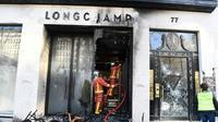 """Les pompiers interviennent sur un feu à la boutique Longchamp, pendant la manifestation des """"gilets jaunes"""", sur les Champs-Elysées  à Paris, le 16 mars 2019 [Alain JOCARD / AFP]"""