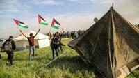 """Des Palestiniens installent des tentes dans la bande de Gaza, près de la frontière avec Israël, en solidarité avec la """"Journée de la terre"""" célébrée à partir de vendredi, le 27 mars 2018 [MAHMUD HAMS / AFP]"""