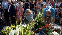 Les passants déposent des fleurs en hommage aux victimes de l'attaque des Ramblas à Barcelone, le 16 août 2018 [Josep LAGO / AFP]