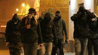 Un groupe d'hommes cagoulés marche le 14 février à Bastia lors d'un rassemblement en soutien à un supporteur du Sporting Club de Bastia blessé à Reims [YANNICK GRAZIANI / AFP]