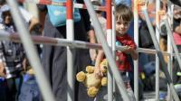 Son ourson à la main, un enfant de réfugiés attend le bus après son arrivée à Munich, le 1er septembre 2015 [CHRISTOF STACHE / AFP]