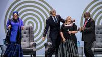L'ex président américain Barack Obama, la veuve de Nelson Mandela, Graça Machel (à gauche) et le président sud-africain Cyril Ramaphosa (à droite) dansent en compagnie de la chanteuse Thandiswa Mazwai lors d'une cérémonie en l'honneur de Mandela, le 17 juillet 2018 à Johannesbourg [MARCO LONGARI / AFP]